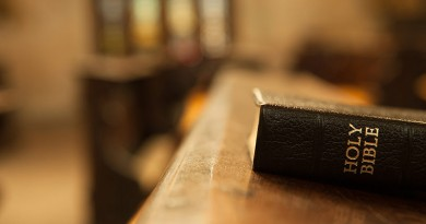 Holy Bible on a wooden church bench.